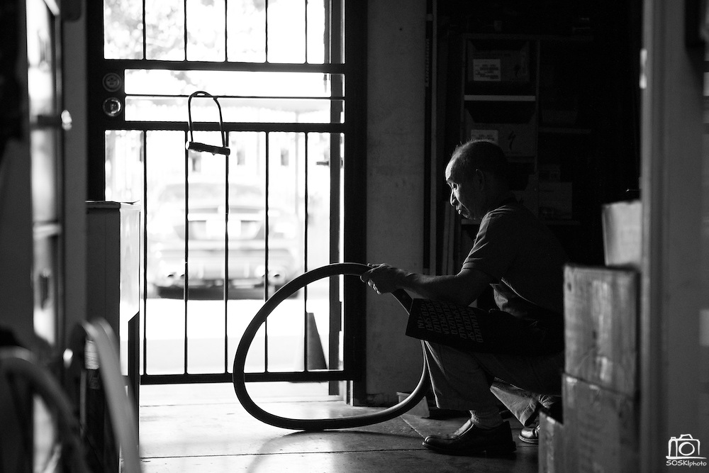 Manager and mechanic Jason Tran inflates a tire tube before installing new wheels on a customer's mountain bike at Sun Bike Shop in Milpitas, Calif., on Sept. 18, 2012.  Tran has been running Sun Bike Shop for over 12 years.  Photo by Stan Olszewski/SOSKIphoto.