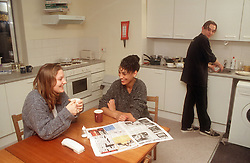 Group of teenagers in communal hostel kitchen,