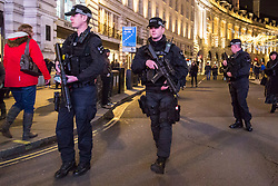 London, December 31 2017. Armed police on Regent Street patrol as revellers in London's West End enjoy the build-up to New Year. © SWNS