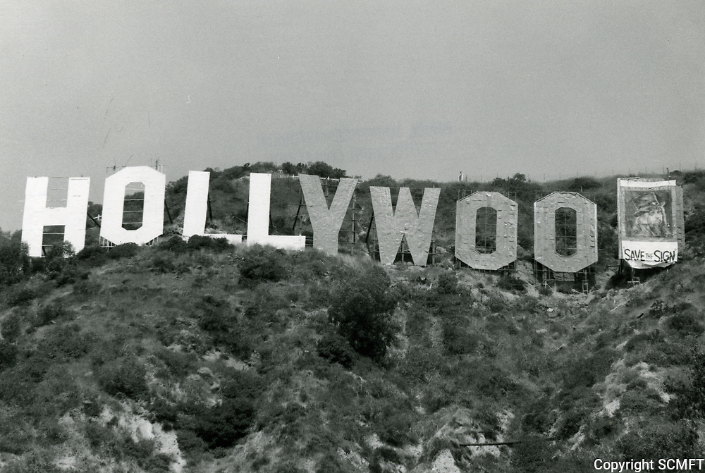 """1973 Refurbishing of The Hollywood sign. A """"save the sign"""" banner featuring Leon Russell covers the letter D."""