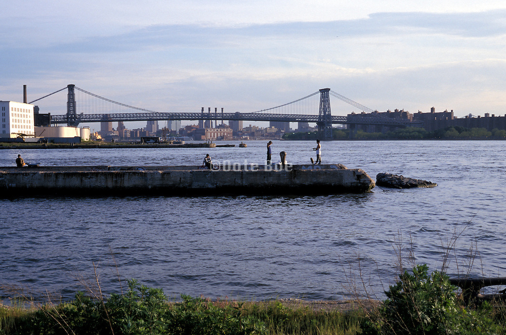 People fishing on a concrete pier East River NYC