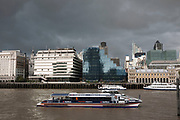 Thames Clipper passes the Northern and Shell building on a grey day in central London. The clipper boats provide water transport for Londoners and tourists alike.