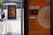 With new local coronavirus lockdown measures now in place and Birmingham currently set at 'Tier 2', people wearing face masks near bus stop Public Health England / NHS digital information poster advising that the local lockdown level is 'High' in the city centre on 14th October 2020 in Birmingham, United Kingdom. This is the first day of the new three tier system in the UK which has levels: 'medium', which includes the rule of six, 'high', which will cover most areas under current restrictions; and 'very high' for those areas with particularly high case numbers. Meanwhile there have been calls by politicians for a 'circuit breaker' complete lockdown to be announced to help the growing spread of the Covid-19 virus.