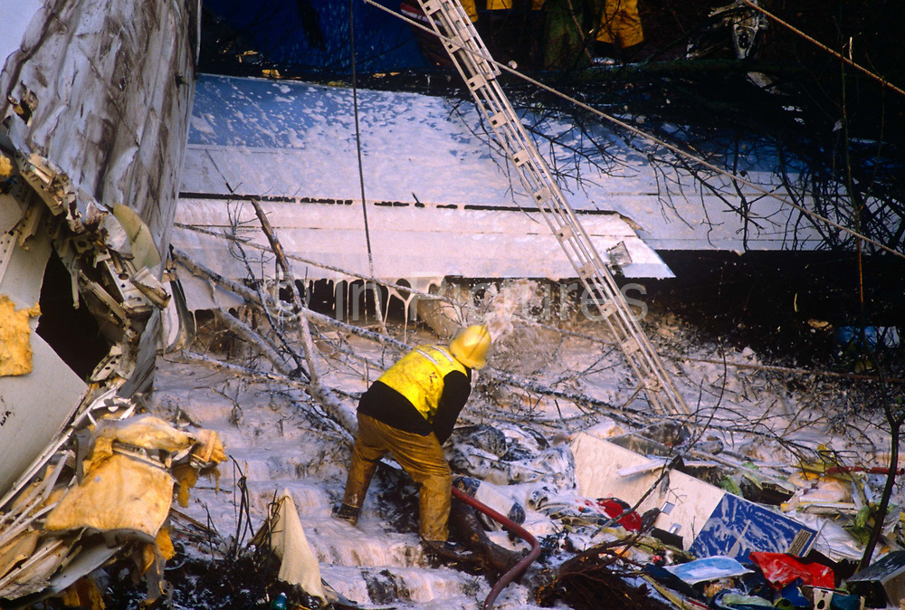 Using ladders and ropes during a rescue operation, a fire fighter sprays foam on to the broken fuselage of a British Midland Airways Boeing 737-400 series jet airliner which lies on an embankment of the M1 motorway at Kegworth, near East Midlands Airport in Leicestershire, England. On the night of 8th January 1989, flight 92 crashed due to the shutting down of the wrong, malfunctioning engine. Attempting an emergency landing, 47 people died and 74 people, including seven members of the flight crew, sustained serious injuries. The aircraft's tail snapped upright at ninety degrees and here perished most of the passenger fatalities. The devastation was hampered by woodland and the fire fighters are attempting to rescue survivors or extract those killed in this air disaster that proved one of Britain's worst.