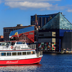 Baltimore, MD / US - October 15, 2016: A cruise boat sails past the National Aquarium in the city's Inner Harbor as it takes passengers on a tour of the waterway.