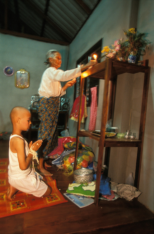 A boy visits his home and prays in front of the family shrine during the Poy Sang Long, the yearly ordination of novice monks, Mae Hong Song, Thailand. His great grandmother lights candles and places them on the shrine.