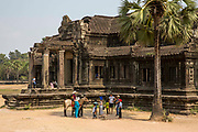 Tourists stand  and pose for photographs outside The Outer Gallery, Angkor Wat, Krong Siem Reap, Cambodia. Angkor Wat is a temple complex in Cambodia and the largest religious monument in the world, with the site measuring 162.6 hectares. It is Cambodia's main tourist destination.