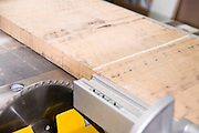 carpenter uses a power saw to cut oak wood