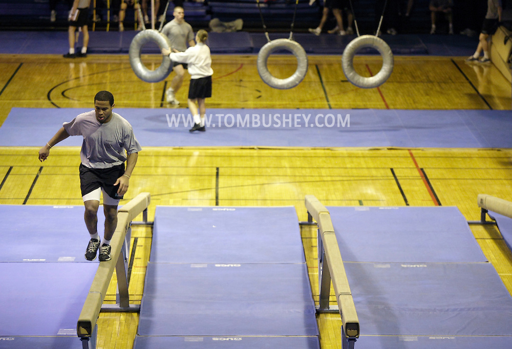 A cadet, at left, does the balance beam traverse  during the Indoor Obstacle Course Test in Hayes Gym at the U.S. Military Academy at West Point on Feb. 9, 2010. The through the tires obstacle in in the background.