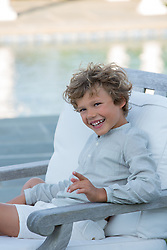 little boy in a chair laughing