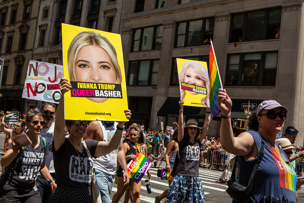 """New York, NY - 25 June 2017. New York City Heritage of Pride March filled Fifth Avenue for hours with groups from the LGBT community and it's supporters. A large contingent of marchers from Rise and Resist, many of whom were carrying signs, the largest of which here has a large photo of Ivanka Trump, with the banner """"Ivanka Trump / Queer Basher"""" superimposed over her mouth."""