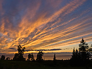 At sunset, lines of orange yellow clouds form patterns against dark blue sky over Cook Inlet, Ninilchik, Alaska, USA. Ninilchik is on the west side of the Kenai Peninsula, 38 miles southwest of Kenai on Sterling Highway, 188 miles by road from Anchorage and 44 miles from Homer. Ninilchik hosts the annual Kenai Peninsula State Fair. The Alaska Native Claims Settlement Act recognized Ninilchik as an Alaska Native village.