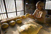 Akbar Zareh, who has worked in a bakery seven days a week since he was a young boy, forms dough in his bakery in Yazd, Iran. (Akbar Zareh is featured in the book What I Eat: Around the World in 80 Diets.) MODEL RELEASED.