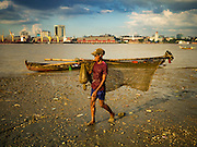 04 NOVEMBER 2015 - YANGON, MYANMAR: A fisherman with his catch and nets walks along the bank of the Yangon River in Dala. Yangon is in the background. Dala is located on the southern bank of Yangon River across from downtown Yangon, Myanmar. Many Burmese live in Dala and surrounding communities and go across the river into central Yangon for work.    PHOTO BY JACK KURTZ