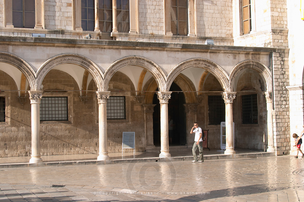 the arched porch and facade of the Sponza palace on the Luza Lodge Loggia Square on the Pred Dvorom street. One tourist walking past Dubrovnik, old city. Dalmatian Coast, Croatia, Europe.