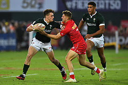 Tomi Lewis of Wales is tackled by David Richard of Canada <br /> <br /> Photographer Craig Thomas/Replay Images<br /> <br /> World Rugby HSBC World Sevens Series - Day 2 - Friday 6rd December 2019 - Sevens Stadium - Dubai<br /> <br /> World Copyright © Replay Images . All rights reserved. info@replayimages.co.uk - http://replayimages.co.uk