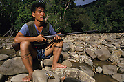 1989: Kelabit native and hunter, Fredrick Ngareng, in his early twenties, with shotgun sitting by the Limbang river. Near Long Napir, Limbang district, Sarawak, Borneo<br /> <br /> Tropical rainforest and one of the world's richest, oldest eco-systems, flora and fauna, under threat from development, logging and deforestation. Home to indigenous Dayak native tribal peoples, farming by slash and burn cultivation, fishing and hunting wild boar. Home to the Penan, traditional nomadic hunter-gatherers, of whom only one thousand survive, eating roots, and hunting wild animals with blowpipes. Animists, Christians, they still practice traditional medicine from herbs and plants. Native people have mounted protests and blockades against logging concessions, many have been arrested and imprisoned.