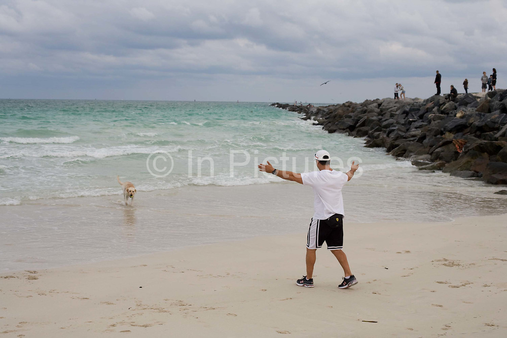 A man calls his golden labrador to him whilst walking the dog at South Pointe Park South Beach Miami beside the Atlantic Ocean