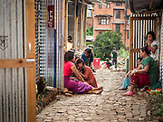 02 AUGUST 2015 - BHAKTAPUR, NEPAL:  Women chat in the alley between shelters in a small Internal Displaced Person (IDP) camp at Durbar Square in Bhaktapur for people left homeless by the Nepal earthquake. The Nepal Earthquake on April 25, 2015, (also known as the Gorkha earthquake) killed more than 9,000 people and injured more than 23,000. It had a magnitude of 7.8. The epicenter was east of the district of Lamjung, and its hypocenter was at a depth of approximately 15 km (9.3 mi). It was the worst natural disaster to strike Nepal since the 1934 Nepal–Bihar earthquake. The earthquake triggered an avalanche on Mount Everest, killing at least 19. The earthquake also set off an avalanche in the Langtang valley, where 250 people were reported missing. Hundreds of thousands of people were made homeless with entire villages flattened across many districts of the country. Centuries-old buildings were destroyed at UNESCO World Heritage sites in the Kathmandu Valley, including some at the Kathmandu Durbar Square, the Patan Durbar Squar, the Bhaktapur Durbar Square, the Changu Narayan Temple and the Swayambhunath Stupa. Geophysicists and other experts had warned for decades that Nepal was vulnerable to a deadly earthquake, particularly because of its geology, urbanization, and architecture.      PHOTO BY JACK KURTZ