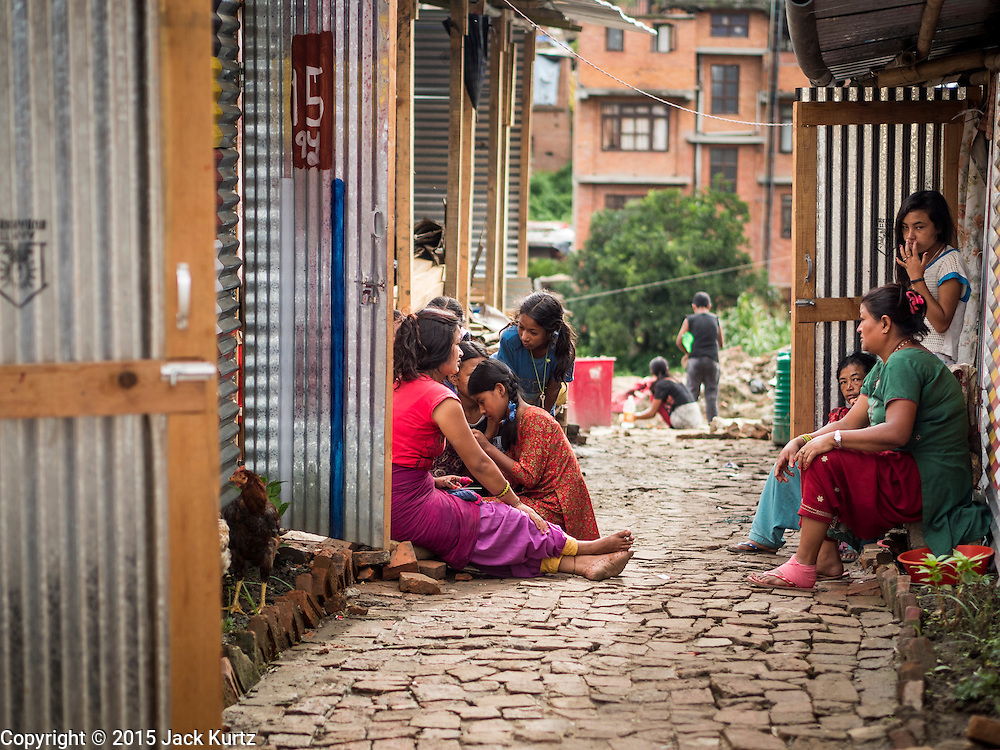02 AUGUST 2015 - BHAKTAPUR, NEPAL:  Women chat in the alley between shelters in a small Internal Displaced Person (IDP) camp at Durbar Square in Bhaktapur for people left homeless by the Nepal earthquake. The Nepal Earthquake on April 25, 2015, (also known as the Gorkha earthquake) killed more than 9,000 people and injured more than 23,000. It had a magnitude of 7.8. The epicenter was east of the district of Lamjung, and its hypocenter was at a depth of approximately 15km (9.3mi). It was the worst natural disaster to strike Nepal since the 1934 Nepal–Bihar earthquake. The earthquake triggered an avalanche on Mount Everest, killing at least 19. The earthquake also set off an avalanche in the Langtang valley, where 250 people were reported missing. Hundreds of thousands of people were made homeless with entire villages flattened across many districts of the country. Centuries-old buildings were destroyed at UNESCO World Heritage sites in the Kathmandu Valley, including some at the Kathmandu Durbar Square, the Patan Durbar Squar, the Bhaktapur Durbar Square, the Changu Narayan Temple and the Swayambhunath Stupa. Geophysicists and other experts had warned for decades that Nepal was vulnerable to a deadly earthquake, particularly because of its geology, urbanization, and architecture.      PHOTO BY JACK KURTZ