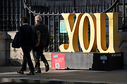 Two businessmen walk past the grammatical personal pronound 'YOU', one of several words located around the City of London, the capital's financial district, on 20th October 2021, in London, England. This word is one of many others along a route around several major attractions including the Millennium Bridge, St Paul's Cathedral, Museum of London and the Barbican Centre and will help orientate the spaces around Culture Mile. Each installation acts as a way finding tool and sculptural attractor where people can be informed about Culture Mile and the area. The distance between each installation allows the pedestrian to be guided between the last and the next word long the route.