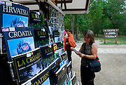 Stall selling souvenirs in Krka National Park, Croatia, with tourist looking at pamphlet.