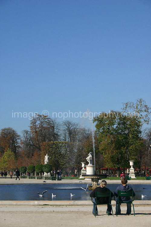 Couple seated at pond in Tuileries gardens, Paris, France<br />