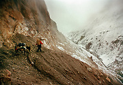 Going over the 4925m Irshad Uween pass, the border between Afghanistan and Pakistan, in our last days trekking.<br /> <br /> Adventure through the Afghan Pamir mountains, among the Afghan Kyrgyz and into Pakistan's Karakoram mountains. July/August 2005. Afghanistan / Pakistan.