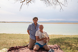 two men and a dog by a lake