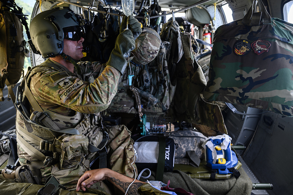 U.S. Army Staff Sgt. Sam Osenga, a critical care flight paramedic with 1st Battalion, 214th Aviation Regiment, prepares an intravenous line in flight to stabilze a simulated casualty during Saber Junction 20, Aug. 18, 2020, at Hohenfels Training Area. Saber Junction 20 is a 7th Army Training Command-conducted, U.S. Army Europe-directed annual exercise designed to assess the readiness of the U.S. Army's 173rd Airborne Brigade to execute unified land operations in a joint, combined environment, and to promote interoperability with participating allies and partner nations. This year's exercise will take place primarily at 7ATC's Grafenwoehr and Hohenfels Training Areas in Bavaria. U.S. military forces stationed in Europe routinely conduct these types of exercises with allied and partner nations to enhance interoperability and readiness. (U.S. Army photo by Sgt. 1st Class Garrick W. Morgenweck)