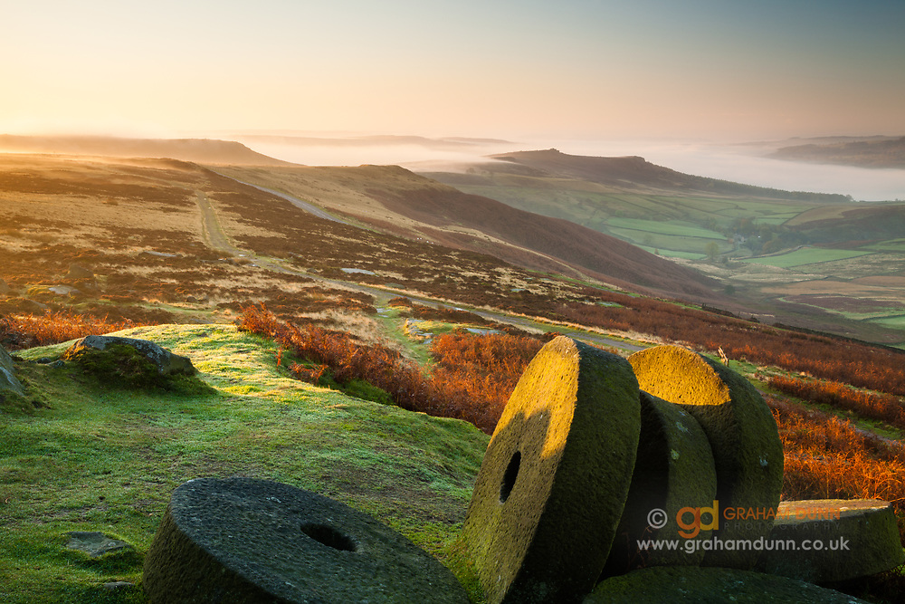 A classic Peak District view at dawn. Stanage millstones provide the foreground with a mist-filled Derwent Valley beyond. A sunrise landscape scene from Derbyshire, England, UK.
