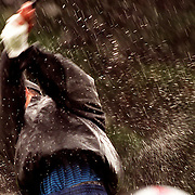 Water sprays off Tiger Woods as he plays his approach shot to the seventeenth in the driving rain during the Australian Open golf tournament on 22 November 1996