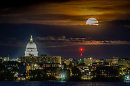 May Supermoon, aka Super Flower Moon and Blood Moon, visible through the clouds over Madison and the Wisconsin Capitol. Atop the dome is the Wisconsin Statue. Photo taken May 26, 2021, from Picnic Point.