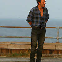 (PPAGE1) Asbury Park 8/2/2002  Bruce Springsteen on the boardwalk of Asbury Park having his photo taken by a photo crew.   He was just north of the carousel building.  Michael J. Treola Staff Photographer..........MJT