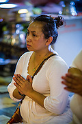 "25 FEBRUARY 2013 - BANGKOK, THAILAND:  A woman prays in Wat Benchamabophit Dusitvanaram (popularly known as either Wat Bencha or the Marble Temple) on Makha Bucha Day. Makha Bucha is a Buddhist holiday celebrated in Myanmar (Burma), Thailand, Cambodia and Laos on the full moon day of the third lunar month (February 25 in 2013). The third lunar month is known in Thai is Makha. Bucha is a Thai word meaning ""to venerate"" or ""to honor"". Makha Bucha Day is for the veneration of Buddha and his teachings on the full moon day of the third lunar month. Makha Bucha Day marks the day that 1,250 Arahata spontaneously came to see the Buddha. The Buddha in turn laid down the principles his teachings. In Thailand, this teaching has been dubbed the 'Heart of Buddhism'.     PHOTO BY JACK KURTZ"