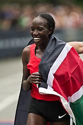 NYRR Mini 10K road race (40th year); Edna Kiplagat, Kenya, winner, draped with flag