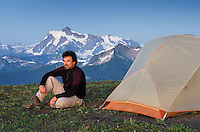 Hiker enjoying the evening at backcountry campsite on Skyline Divide, Mount Baker Wilderness Washington