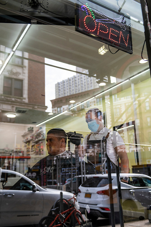 New York City, USA - March 21, 2020: Rafael Peralto, age 48, wears a face mask at his barbershop while cutting the hair of customer Freddy Munoz in the Washington Heights neighborhood of Manhattan.