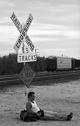 sexy man resting against a railroad crossing sign