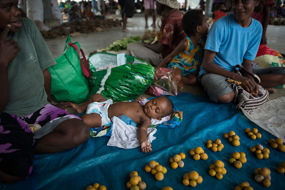 A baby naps at the open-air market in Madang, Papua New Guinea