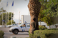 An Afghan child hides himself behind a palm tree to avoid border police at the international port of Patras. He hopes to smuggle himself on a boat bound for Italy. Greece. October 2010.