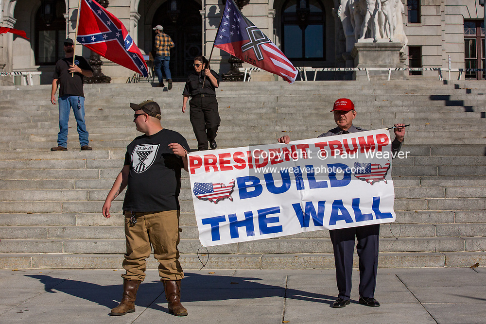 """Harrisburg, PA -- Arthur Jones (right), wearing a Make America Great Again hat, holds a sign reading """"President Trump Build the Wall"""" at a 2016 rally of white supremacists at the Pennsylvania State Capitol."""