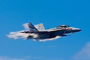 An F-18E breaks the sound barrier during an airshow onboard the USS Abraham Lincoln.