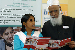 Elderly Asian man looks at leaflets about dementia with a health worker at an NHS roadshow to educate the public about the disease; Yorkshire,