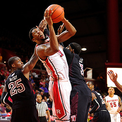 Kadeem Jack #11 of the Rutgers Scarlet Knights goes up for a basket between Quenton DeCosey #25 and Anthony Lee #3 of the Temple Owls during the second half of Rutgers men's basketball vs Temple Owls in American Athletic Conference play on Jan. 1, 2014 at Rutgers Louis Brown Athletic Center in Piscataway, New Jersey.