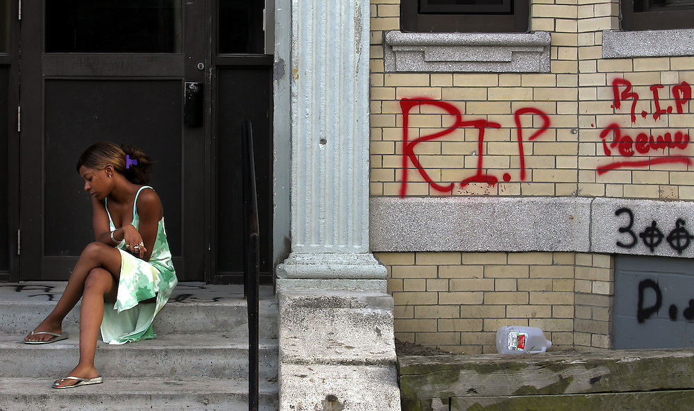 """(073006-Roxbury, MA)  Shareta, 18, sits just past a memorial dedicated to Vernon """"Peewee"""" Cobb, who was killed in gang related violence the day before in Roxbury."""