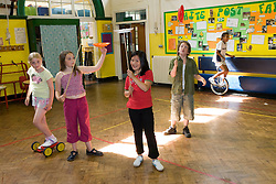 Group of children practising circus tricks in school sports hall,