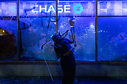 OAKLAND, CA - MAY 29: A protester smashes the window of a Chase bank in Downtown Oakland during protests against the death of George Floyd in police custody, in Oakland, California on May 29, 2020. (AP Photo/Philip Pacheco)