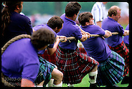 Team of men yanks on rope in tug-of-war contest at the Highland Games in Inverness. Scotland
