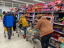 © Licensed to London News Pictures. 22/12/2020. London, UK. Queues form in the aisles in Asda in South West London after a rush of Christmas shoppers descend  on the store causing long queues and empty shelves after news of a French travel ban to Europe which has blocked freight from leaving the Port of Dover after a spike of infections due to the Covid-19 mutation. Last week Prime Minister Boris Johnson put London and parts of the South East into Tier 4 lockdown after the new Covid-19 mutation was discovered. Photo credit: Alex Lentati/LNP